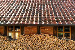 Stacked firewood next to a brick wall of house Stock Image