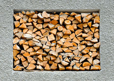 Stacked firewood in the wall Stock Image
