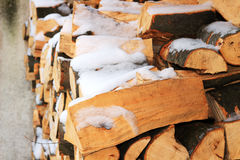 Stacked firewood in winter under the snow Stock Photo