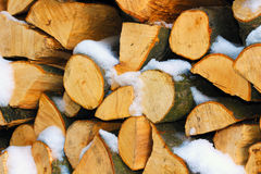 Stacked firewood in winter under the snow Stock Images