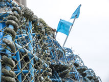 Stacked fishing nets. With blue flags Stock Photos