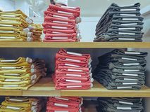 Stacked Folded Colorful Jeans on Shelf at Clothing Store. Stacked Folded Colorful Denim Jeans on Shelf at Clothing Store Stock Images