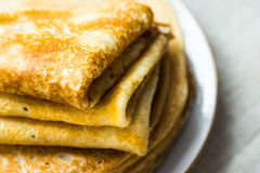 Stacked folded crepes on white plate on linen cloth background, closeup, breakfast Stock Image