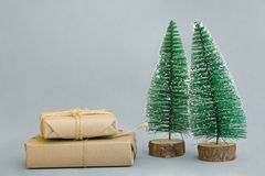 Stacked gift boxes wrapped in craft paper tied with twine Christmas trees on grey background. New Year corporate presents shopping stock photography