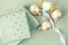 Stacked gift boxes wrapped in grey silver paper with polka dots pattern. Wooden spool with white silk ribbon, Christmas balls. Stacked gift boxes wrapped in Royalty Free Stock Images