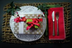 Stacked gifts Christmas holiday dinner background with white plate and red napkin. Horizontal aspect Stock Photos