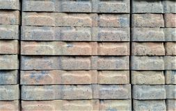 Stacked Gray and Red Landscape Tiles on Warehouse Shelf. Red and gray brick landscaping tile in stacks on DIY warehouse shelf Royalty Free Stock Images