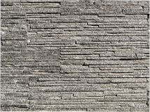 Stacked grey thin slate bricks background photograph. Uneven and rough texture. Modern, natural luxury style. Thin slate bricks, authentic photograph shot royalty free stock image
