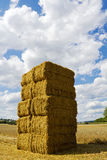 Stacked hay bales against blue summer sky with clouds Royalty Free Stock Photos