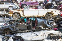 Indianapolis - Circa September 2017: Stacked junk yard clunker cars prepared for crushing to be recycled XII. Stacked junk yard clunker cars prepared for Royalty Free Stock Photography