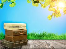 Stacked leather luggage on wood plank with blue sky and sun light background. Travel concept.Best journey with fantasy nature. Background stock image