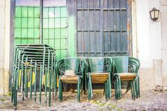 Stacked green tables and chairs on Lisbon street, Portugal. Stacked and locked green tables and chairs on Lisbon old street, Portugal Royalty Free Stock Photo