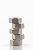 Stacked metal nuts on white background. Stock Photography