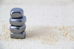 Stacked Metallic Stones on Sand Royalty Free Stock Photography