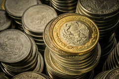 Stacked Mexican Peso Coins. A golden coin with an eagle over stacks of silver coins, business wealth and success concept Royalty Free Stock Images
