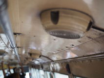 Stacked monkey bar and old speaker attached on ceiling in Thai public bus. Stacked hand holding iron metal bar extended to the front, and old yellow white dirty Royalty Free Stock Photos