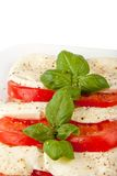 Stacked Mozzarella slices. Some Mozzarella slices stacked with tomatoes and basil Stock Photo