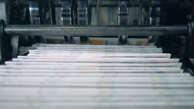 Stacked newspaper on automated conveyor, typography facility. 4K stock video
