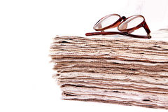 Stacked newspapers and reading glasses Royalty Free Stock Photo