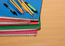 Stacked notebooks with pens and pencils. On a wooden desk Royalty Free Stock Image