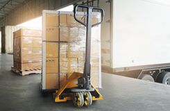 Free Stacked Of Package Boxes On Pallet With Hand Pallet Truck. Trailer Truck Parked Loading At Dock Warehouse. Cargo Shipment Boxes. Stock Photo - 217416040