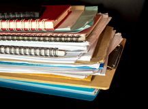 Stacked of office documents paper in the black background. Stacked of office documents paper and notebook in the black background stock image