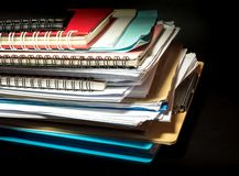 Stacked of office documents paper in the black background. Stacked of office documents paper and notebook in the black background stock images