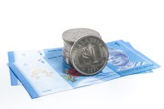 Stacked of old Malaysia Coins on two new Malaysia notes. On a white background Royalty Free Stock Photo