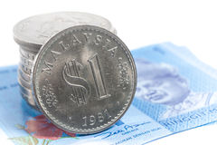 Stacked of old Malaysia Coins on two new Malaysia notes. On a white background Royalty Free Stock Image