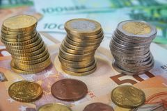Stacked one and two Euro coins with paper banknotes.  Royalty Free Stock Images
