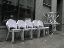 Stacked Outdoor Chairs & Tables in Portland, Oregon. This is a black & white image of stacked tables and chairs on the sidewalk outside a cafe in Portland stock photos