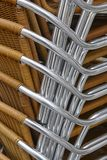 Stacked outdoor metallic and plastic chairs. City background. Vertical Royalty Free Stock Photo