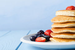 Stacked Pancakes and Fruit. A stack of breakfast pancakes topped with a strawberry, standing on a white china plate, surrounded by Summer fruits.  Pale blue Royalty Free Stock Photography