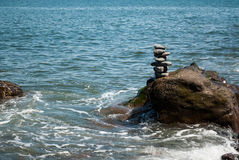 Stacked Pebble Tower being Washed by Wave. Pebbles stacked on a rock in shallow sea with wave washing around it Stock Photography