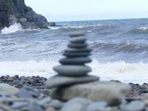 Stacked tower pebbles on a beach. Beach scene of  pebbled beach with  blur stacked tower pebbles of different size pebbles, blue sea with cliffs in the Royalty Free Stock Photos