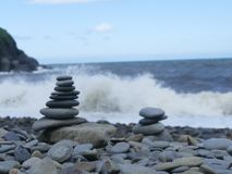 Stacked tower pebbles on a beach. Beach scene of pebbled beach with stacked tower pebbles of different size pebbles, blue sea with cliffs in the background Royalty Free Stock Photos