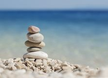 Stacked pebbles on the beach. Stacked pebbles on a beach in the city of Bol island of Hvar with a blue sea background. The whole picture gives the sensation of Stock Photo