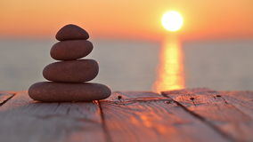 Stacked pebbles and setting sun stock footage