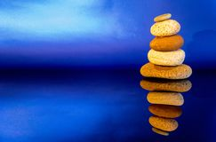 Stacked Pebbles. Small pebbles stacked on top of each other against a black and blue background stock photos