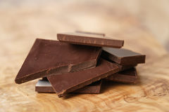 Stacked pieces of chocolate bar on wooden table. Shallow focus Royalty Free Stock Photo