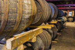 Stacked pile of old wooden barrels and casks in aging cellar at. Whisky distillery in Scotland Royalty Free Stock Photo