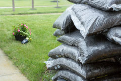 Stacked plastic bags of mulch and flowers in rain Stock Images