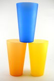 Stacked plastic party cups. Three colored plastic party cups stacked and on white background stock images