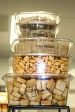 Stacked plastic to go containers holding assorted dry ingredients with different measurements written on them to demonstrate how m royalty free stock photo