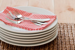 Stacked plates with forks. A table is ready to be set with 6 white bistro plates and silver forks set a top a red polka dot napkin Stock Image