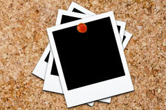 Stacked Polaroid Polaroids Blank Corkboard. Three blank polaroids stacked and affixed on cork board with red small thumb tack Royalty Free Stock Photo