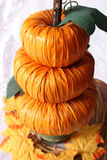 Stacked Pumpkins. Fall decor of pumpkins - three stacked high in container atop raffia over white Stock Image