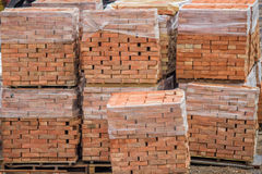 Stacked red clay bricks on pallets Stock Images