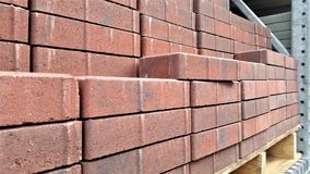 Stacked Red Landscape Tiles on Warehouse Shelf. Red brick landscaping tile in stacks on DIY warehouse shelf Royalty Free Stock Photography