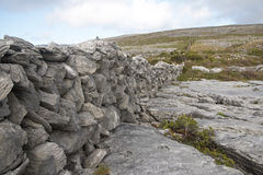 Stacked rock wall cuts through The Burren limestone karst Stock Photo